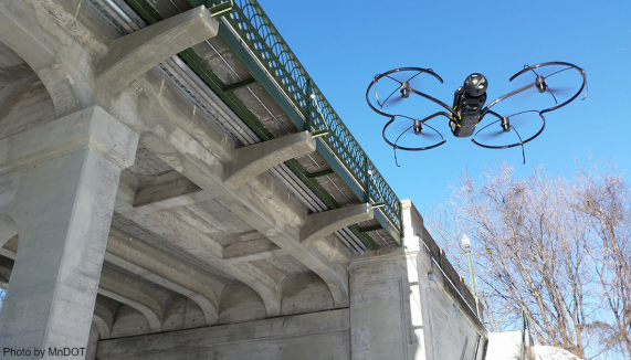 A drone flies next to a bridge. Image credit for this photos belongs to MnDOT.